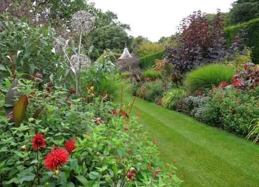Red dahlia and allium sculpture at Hidcote Garden