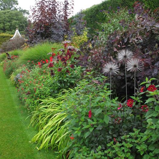 Metal alliums and red foliage in Hidcote's red border